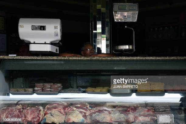 A butcher leans on the counter during a power cut in Caracas on July 31 2018 A power failure cut electricity to 80 percent of the Venezuelan capital...