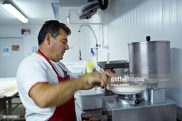 Butcher making hamburger meat at slaughterhouse