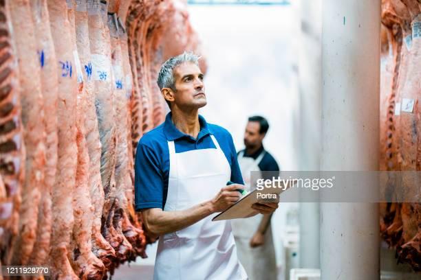 肉屋で質の高いレポートを作る肉屋 - 食肉処理場 ストックフォトと画像