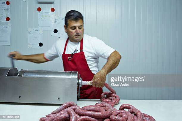 Butcher making sausages at slaughterhouse