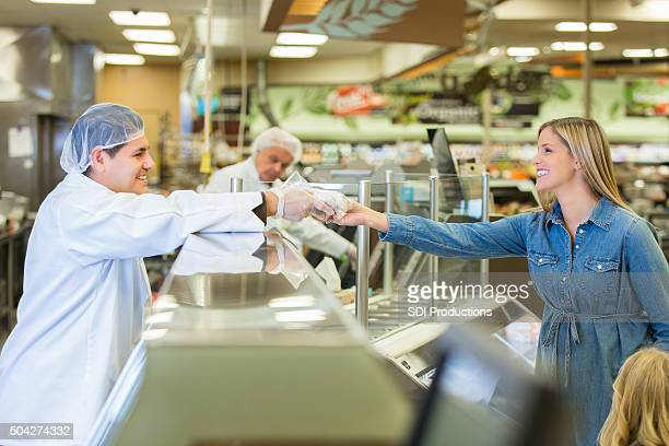 butcher or deli manager assisting customer in local supermarket - delicatessen stock pictures, royalty-free photos & images