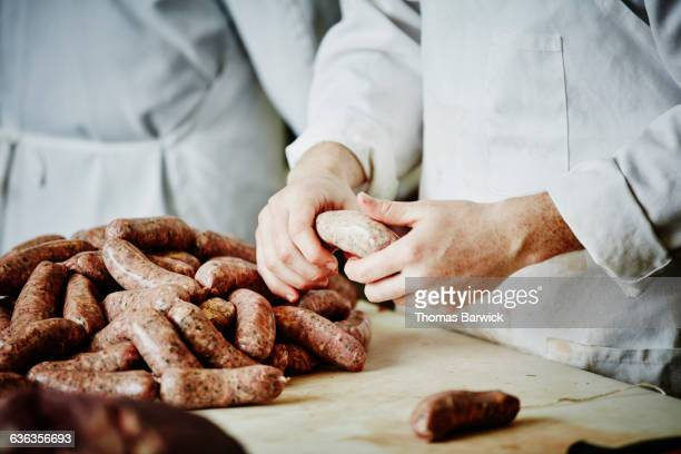 butcher preparing sausage links at workbench - sausage stock pictures, royalty-free photos & images