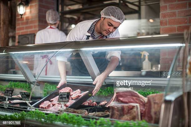 Butcher putting fresh meat on display in butchery