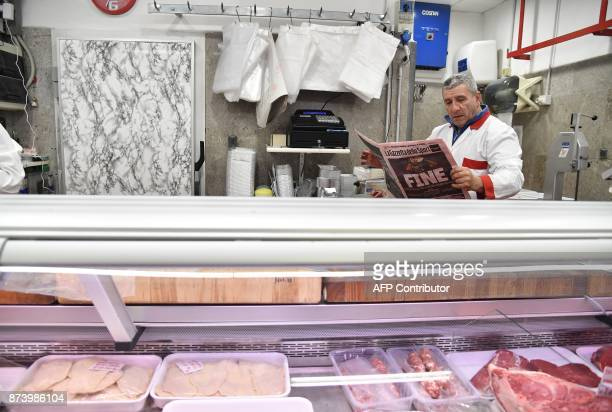 A butcher reads Italian sport newspaper 'Gazetta dello Sport' with a front page reading 'End' a day after the elimination of Italy during the FIFA...