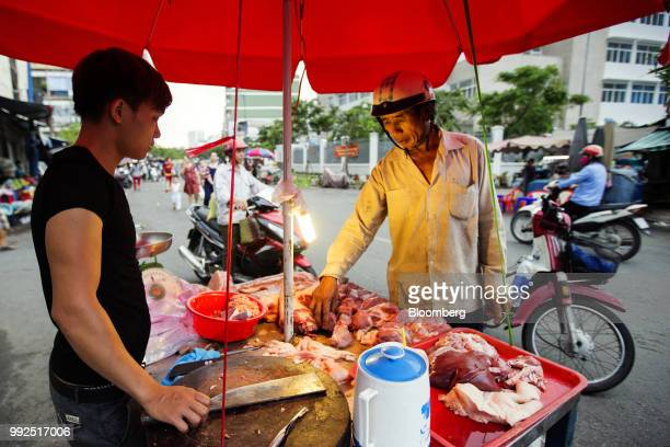 A butcher serves meat to a customer at a roadside stall in Ho Chi Minh City Vietnam on Wednesday June 20 2018 For decades Vietnamese have shopped...