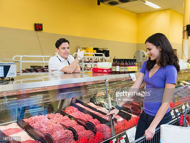 Butcher serving customer at meat counter of grocery store