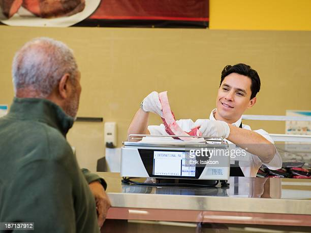 Butcher serving customer meat counter of grocery store