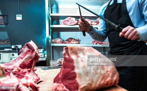 Butcher sharpening knife on knife steel in butchers shop, mid section