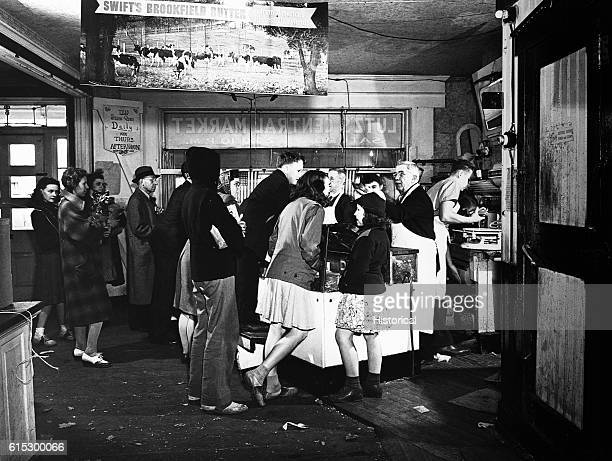 Butcher shop owner Benjamin Lutz helping customers at 430 PM when the factories change shifts Lititz Pennsylvania November 1942