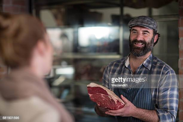 Butcher showing meat to woman in butchery