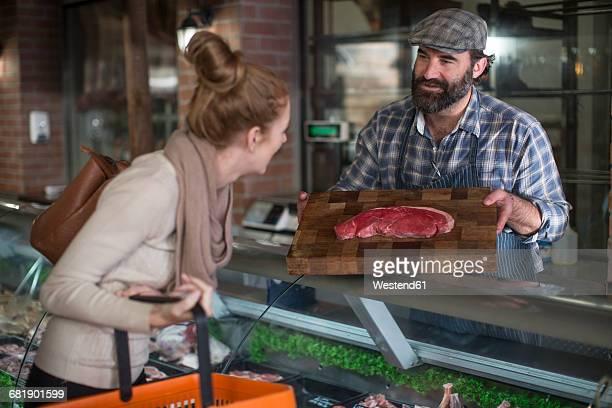 butcher showing meat to woman in butchery - boucher photos et images de collection