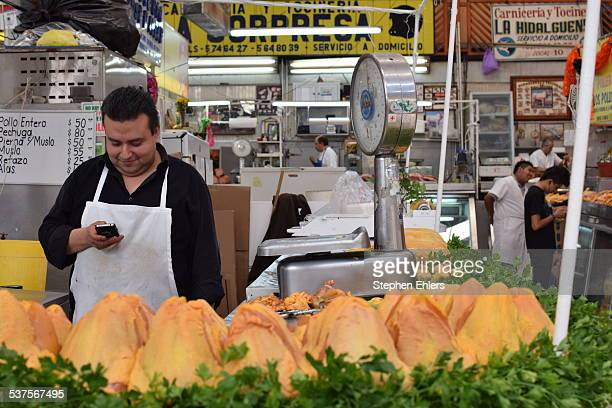 A butcher smiles and looks at his smart phone behind a row of whole chickens at his stall in Mercado Medellin in Mexico City Scales market stalls and...