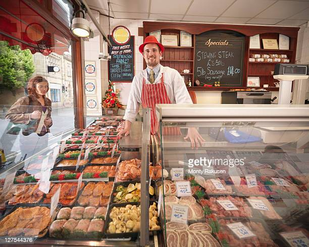 butcher standing behind counter in shop - delicatessen stock photos and pictures