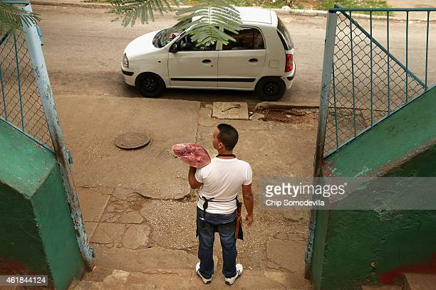 A butcher stands out on the sidewalk in front of Mercado Agropecuario in an attempt to drum up business in the Vedado neighborhood of Havana January...
