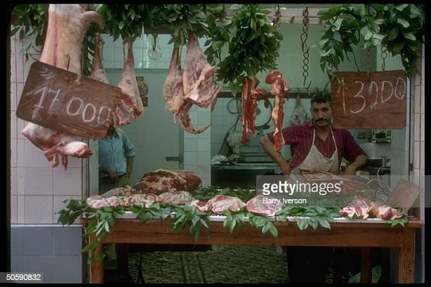 Butcher striking wry stance holding sway at foliage garnish attractive meat counter display opentoair in casbah area of Algiers Algeria