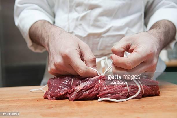 Butcher tying beef tenderloin with string