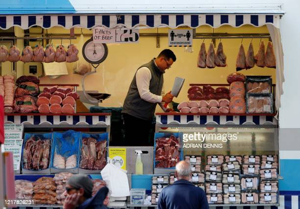 A butcher uses his cleaver at the outdoor market in Basingstoke on June 6 as lockdown measures ease during the novel coronavirus COVID19 pandemic...