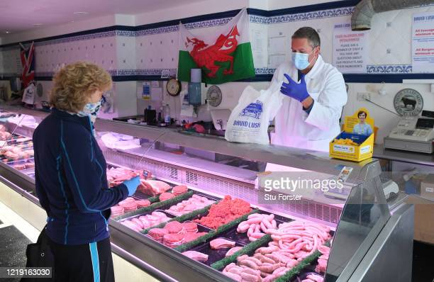 A butcher wearing a protective mask and gloves serves a customer wearing a scarf around her mouth at David Lush butchers on April 16 2020 in Penarth...