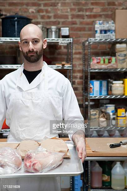 Butcher with tray of meat