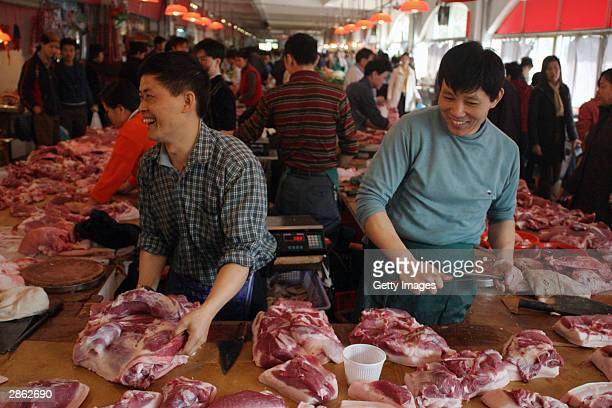 Butchers are busy at a market January13, 2003 in Shenzhen, China. Health officials dismissed the case of a man from Shenzhen who alledgedly got...