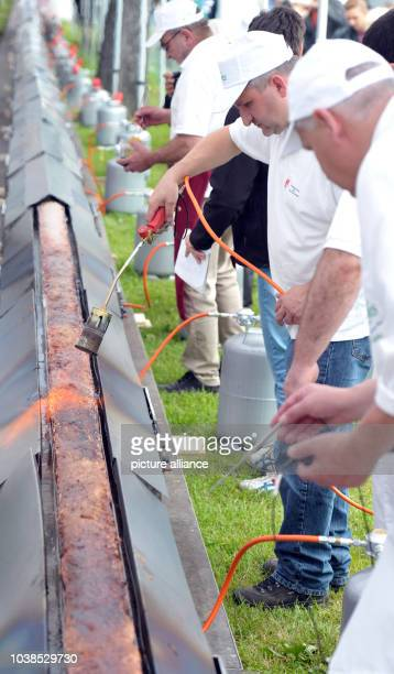 Butchers prepare a Leberkaese a meat loaf variety found in Germanspeaking areas in Ulm Germany 12 June 2016 The butcher's guild used 15 tons of meat...