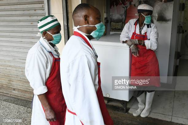 Butchery workers stand outside their shop as they watch a staff member of Kenya's Ministry of Health spraying disinfectant at the city market to curb...