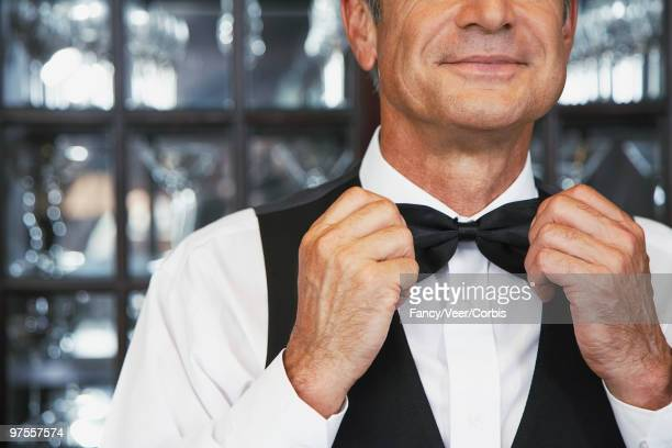Butler adjusting bow tie