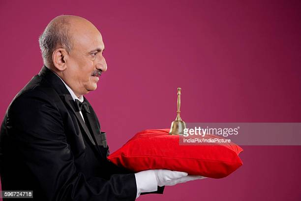 butler carrying a bell - cushion stock photos and pictures