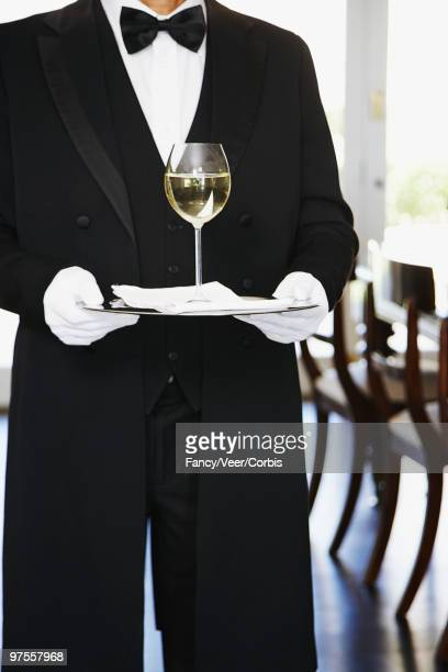 Butler carrying glass of wine on silver tray