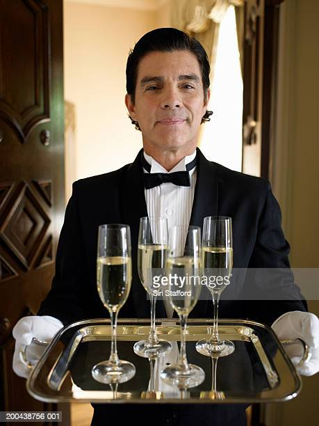 butler carrying tray with champagne flutes - オールバック ストックフォトと画像