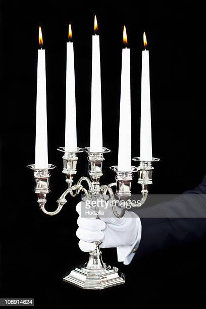 A butler holding a candelabra with lit candles, focus on hand