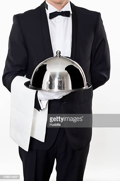 A butler holding a domed tray