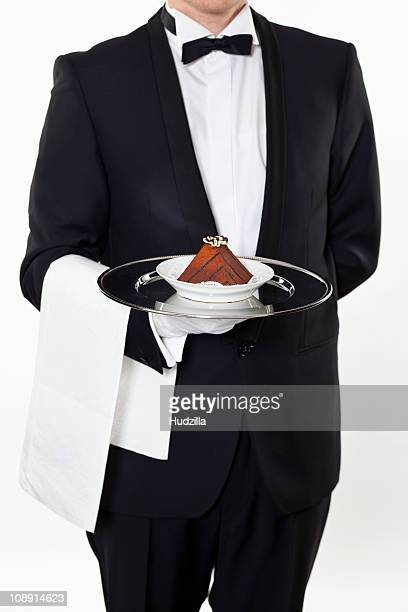 A butler holding a slice of a cake on a silver tray, midsection