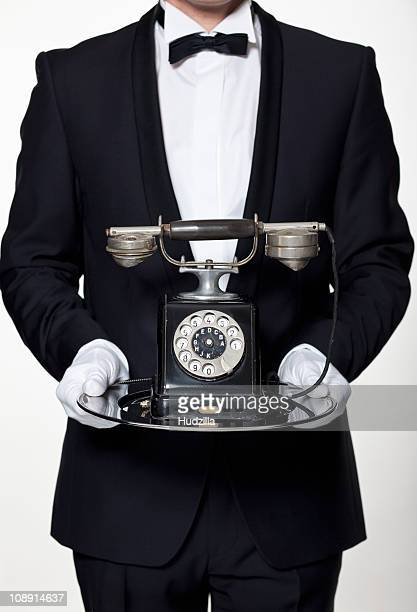A butler holding an antique rotary phone on a silver tray, midsection