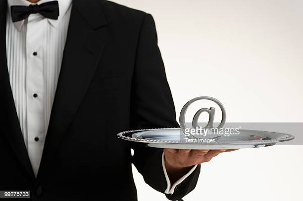 Butler holding at symbol on silver tray