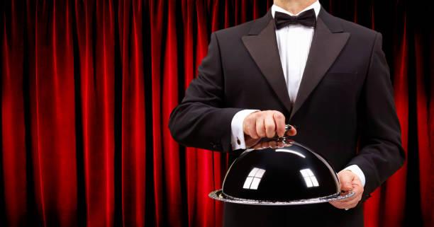 Butler holding domed serving dish