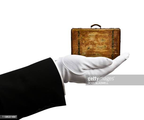 butler holding small tatty leather suitcase - leather stock pictures, royalty-free photos & images