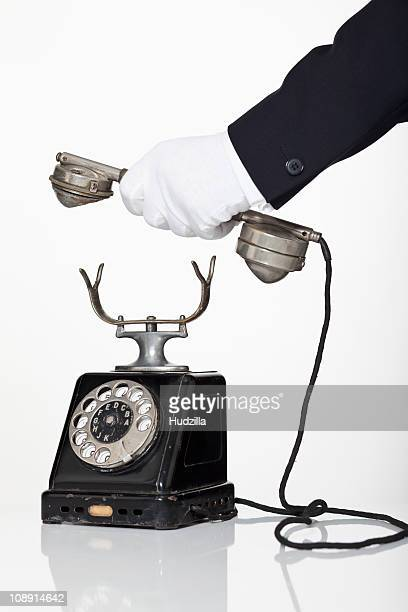 A butler holding the receiver of a rotary phone, focus on hand