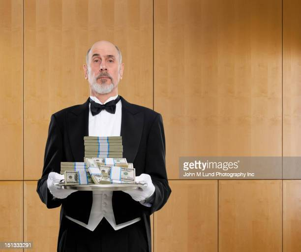 butler holding tray of cash - millionnaire stock photos and pictures