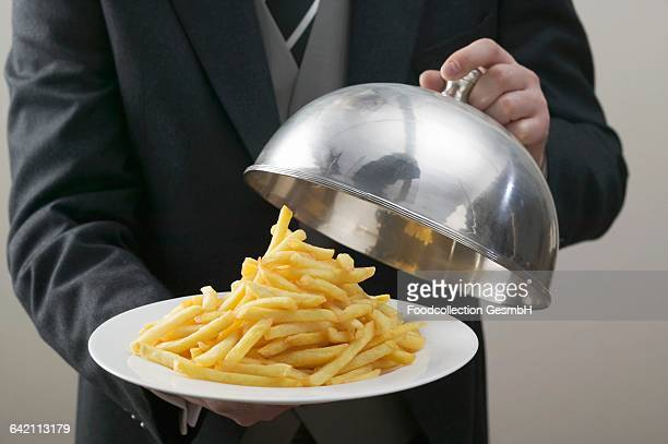 Butler lifting serving dome from plate of chips