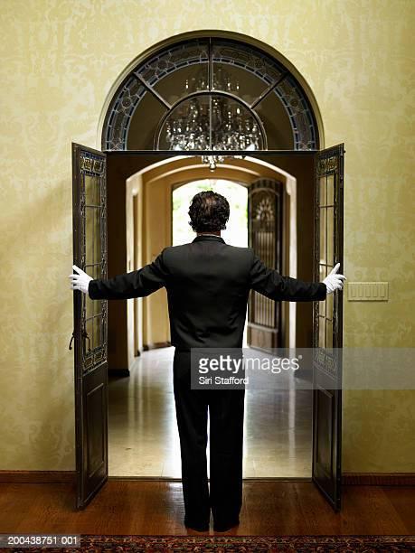 Butler opening double doorway, rear view