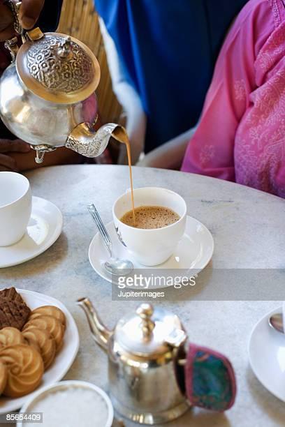 Butler pouring tea for women