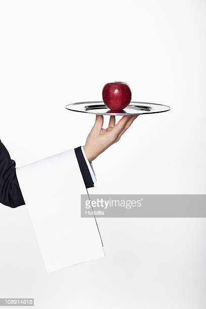 A butler presenting an apple on a silver tray, focus on hand