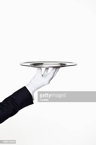 a butler presenting an empty silver tray, focus on hand - élégance photos et images de collection