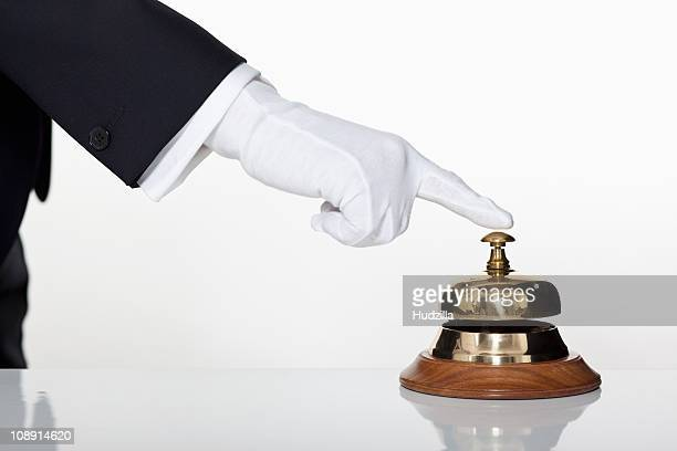 A butler pressing a service bell, focus on hand