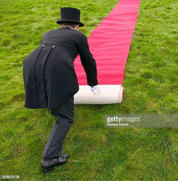 butler rolling red carpet across field - de rola imagens e fotografias de stock