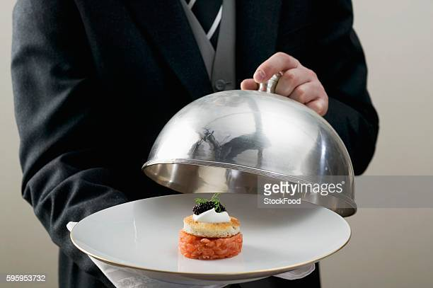 butler serving salmon tartare on plate with domed cover - campana fotografías e imágenes de stock