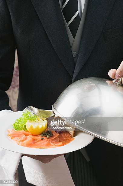 Butler serving smoked salmon with toast, close up, mid section