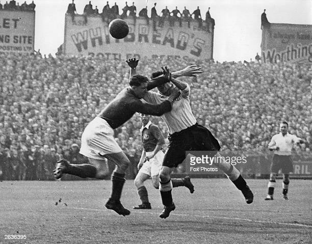 Butler the goalkeeper for Portsmouth FC and McDonald the Fulham FC centreforward struggle for the ball during a 1st division FA league match at...