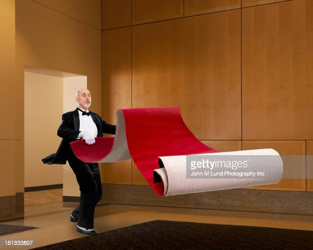 butler unrolling red carpet - red carpet event stock pictures, royalty-free photos & images